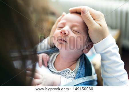 Close up of unrecognizable young mother with her newborn baby son in sling at home