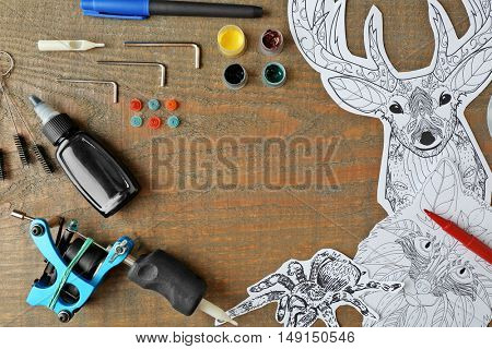 Tattoo machine and supplies on wooden background