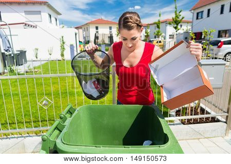 Woman emtying paper waste into trash bin