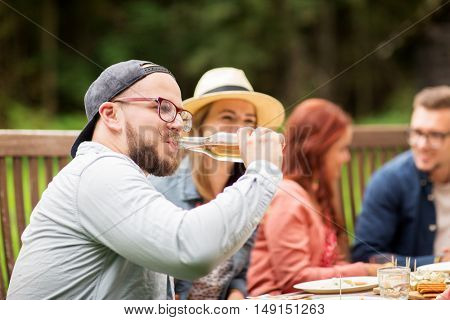 leisure, holidays, eating, people and food concept - happy man drinking beer from bottle at dinner with friends at summer garden party