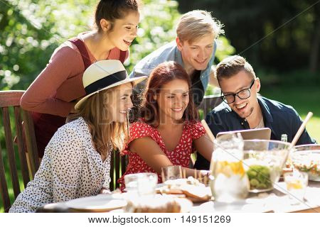 leisure, holidays, gathering, people and technology concept - happy friends with tablet pc computer having dinner at summer garden party