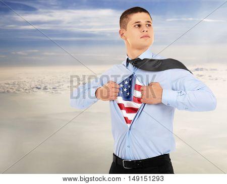 Businessman showing USA flag under suit on sky background.
