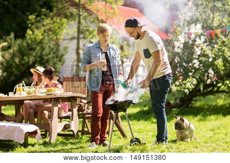 leisure, food, people and holidays concept - friends cooking meat on barbecue grill at summer outdoor party