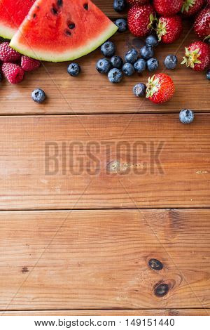 healthy eating, food, dieting and vegetarian concept - close up of raspberry with strawberry, blackberry and watermelon slices on wooden table