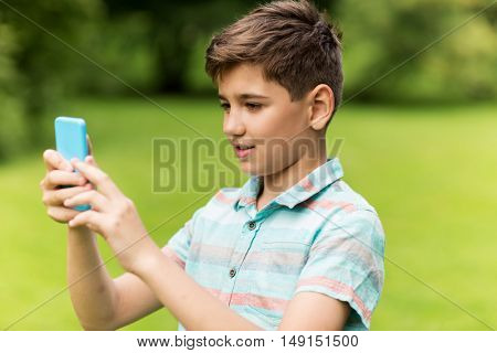childhood, augmented reality, technology and people concept - boy with smartphone playing game in summer park