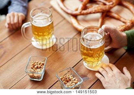 people, leisure and drinks concept - close up of male hands with beer mugs and pretzels at bar or pub