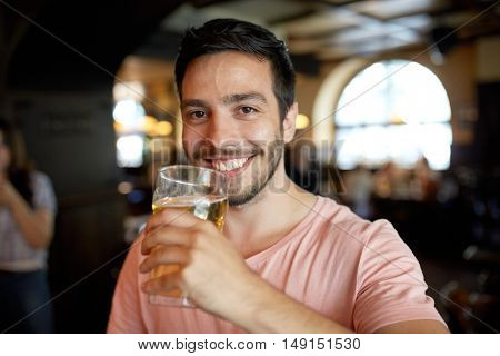 people, drinks, alcohol and leisure concept - close up of happy young man drinking beer at bar or pub