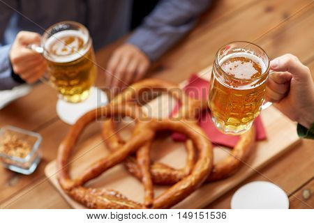 people, leisure and drinks concept - close up of male hands with beer mugs and pretzels on table at bar or pub