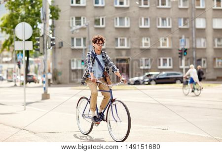 people, style, leisure and lifestyle - young hipster man with shoulder bag riding fixed gear bike on city street