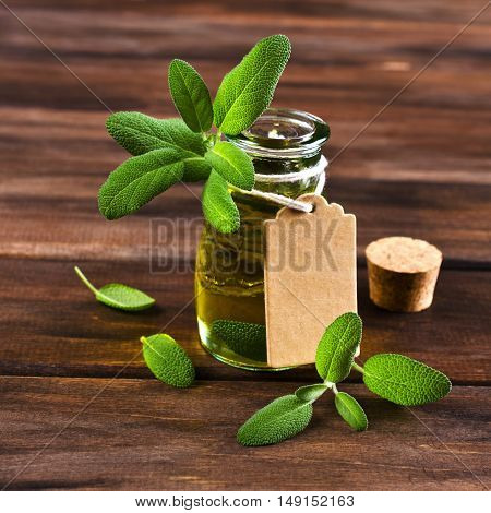 Oil with dry leaves of sage on a wooden background. Selective focus.