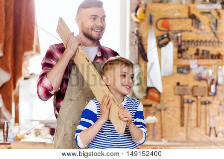 family, carpentry, woodwork and people concept - happy father and little son carrying wood plank at workshop