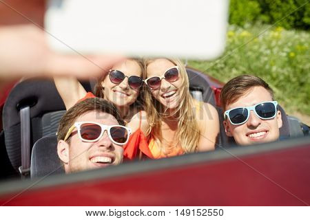 leisure, road trip, travel and people concept - happy friends driving in cabriolet taking selfie by smartphone outdoors