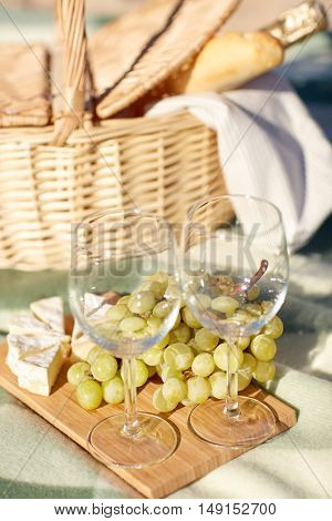 food, holidays and celebration  concept - close up of picnic basket with grapes, wine glasses, cheese and champagne bottle on summer beach