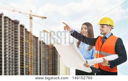 Woman and engineer in vest holding engineering blueprint on building construction background