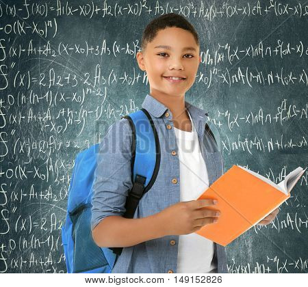 Cute boy with book and backpack on chalkboard background. School concept.