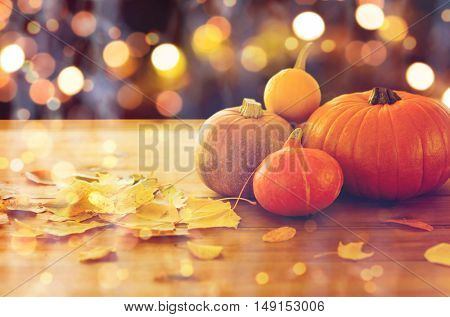 food, halloween, harvest, season and autumn concept - close up of pumpkins and leaves on wooden table over holidays lights