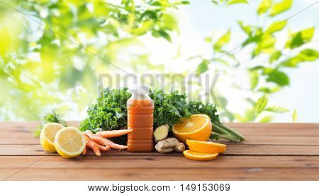 healthy eating, food, dieting and vegetarian concept - bottle with carrot juice, fruits and vegetables on wooden table over green natural background