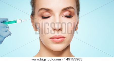 people, cosmetology, plastic surgery and beauty concept - beautiful young woman face and beautician hand in glove with syringe making injection over blue background