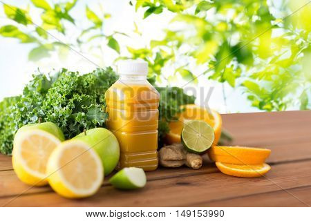 healthy eating, food, dieting and vegetarian concept - bottle with orange juice, fruits and vegetables on wooden table over green natural background