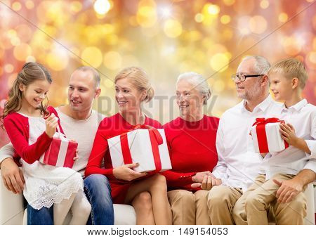 family, holidays, generation, christmas and people concept - happy family with gift boxes sitting on couch over lights background