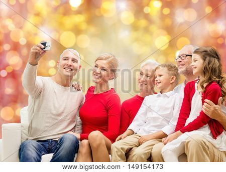 family, holidays, generation, christmas and people concept - smiling family with camera making selfie and sitting on couch over lights background
