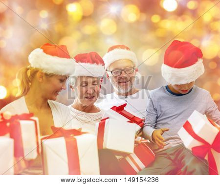 christmas, generation, holidays and people concept - happy family in santa helper hats with gift boxes sitting on couch over lights background