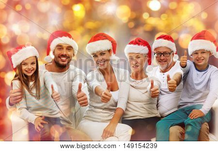christmas, generation, holidays and people concept - happy family in santa helper hats sitting on couch and showing thumbs up gesture over lights background