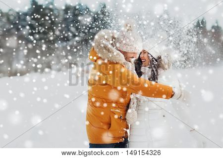 people, season, love and leisure concept - happy couple hugging and laughing outdoors in winter