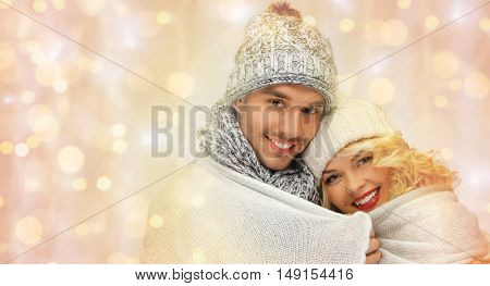 people, christmas, holidays and new year concept - happy family couple in winter clothes wrapped in plaid over holidays lights background