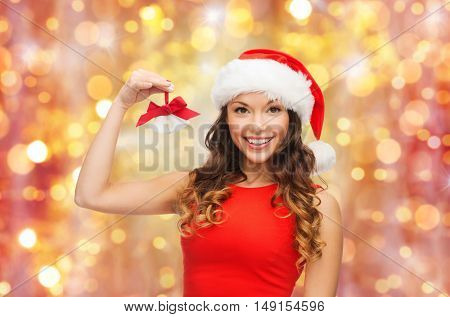 christmas, x-mas, winter and people concept - smiling woman in santa helper hat with jingle bells over holidays lights background
