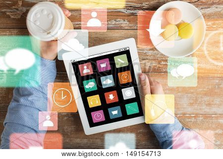 business, media, people and technology concept - close up of male hands with menu icons on tablet pc computer screen, cookies and coffee cup on wooden table