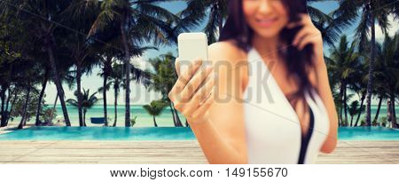summer, travel, tourism, technology and people concept - close up of sexy young woman taking selfie with smartphone over resort beach with palms and swimming pool background