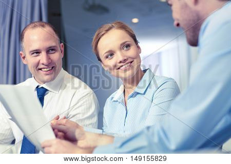 business, people and teamwork concept - smiling business team with papers meeting and talking in office