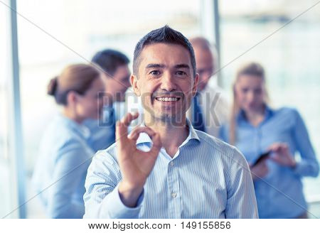 business, people and teamwork concept - smiling businessman showing ok gesture with group of businesspeople meeting in office