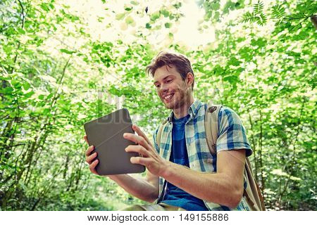 adventure, travel, tourism, hike and people concept - happy young man with backpack and tablet pc computer in woods