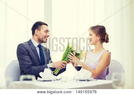 restaurant, couple and holiday concept - smiling man giving girlfriend or wife bouquet of flowers at restaurant