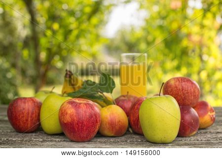 fruits and peach juice on a wooden table, outdoor