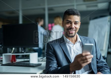 African american businessman texting in the office.