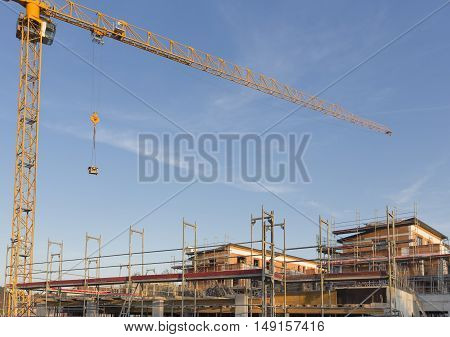 Construction site with yellow crane and blue sky, Germany