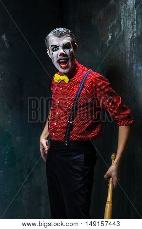The scary clown and baseball-bat on dack. Halloween concept of horror and murderer