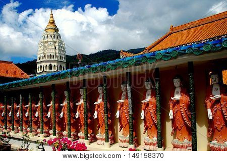 Penang Malaysia - January 8 2008: A row of Buddha statues lines a courtyard arcade and the majestic seven-story grand pagoda at 1891 Kek Lok Si Temple