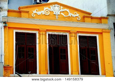 Kuala Lumpur Malaysia - December 24 2007: Restored Chinese shop house with bas relief designs on its cornice and windows with wooden shutters in the Little India district