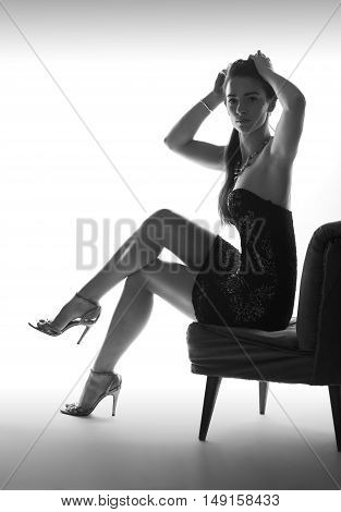 Beautiful sitting woman instudio with high heel shoes, white background