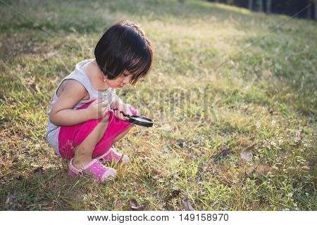 Asian Chinese Little Girl Exploring With Magnifying Glass