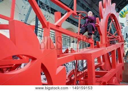 MOSCOW, RUSSIA - DEC 20, 2014: Girl (with model release) sits on red mechanism in pavilion Space at exhibition Miracle Mechanics at VDNKH