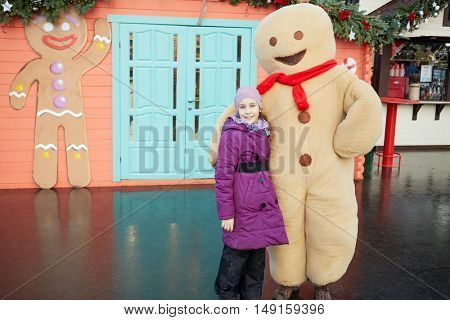 MOSCOW, RUSSIA - DEC 20, 2014: Girl (with model release) and Gingerbread Man near cafe decorated for Christmas holidays at VDNKH.