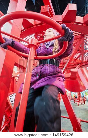 MOSCOW, RUSSIA - DEC 20, 2014: Girl (with model release) on red mechanism  in pavillion Space at exhibition Miracle Mechanics at VDNKH.