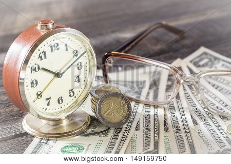 Time is money finance concept with old vintage clocks, dollar bills, spectacles and euro coins.