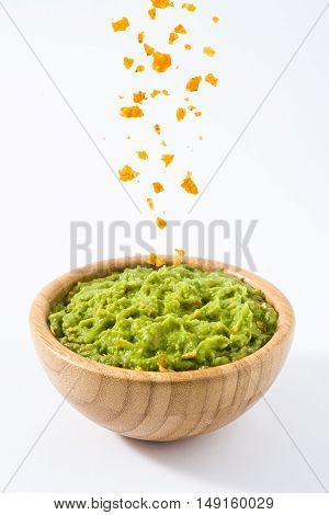 Pouring nachos in a bowl with guacamole