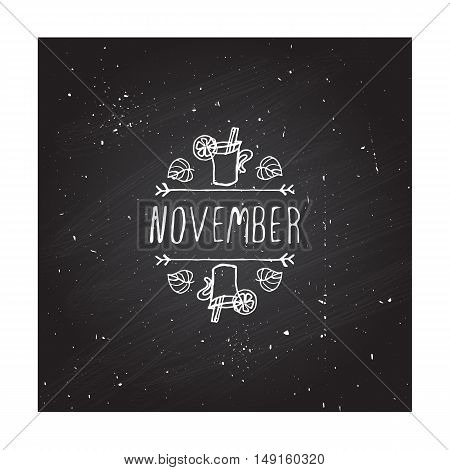 Hand-sketched typographic element with mulled wine, leaves and text on blackboard background. November
